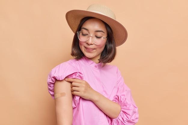 La donna asiatica alla moda in camicetta rosa occhiali e cappello guarda intonacato ottiene l'immunità vaccinata contro il covid 19 mostra la spalla con cerotto dopo il colpo posa al coperto