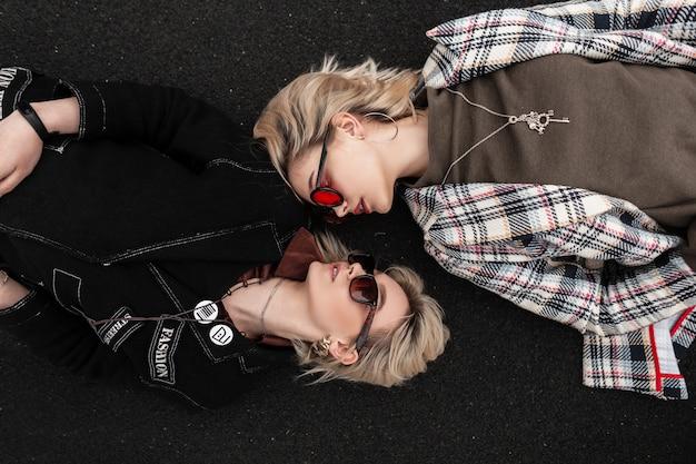 Donne attraenti alla moda in abiti vintage alla moda con occhiali da sole alla moda si rilassano sull'asfalto e si guardano l'un l'altro