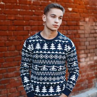 Il giovane attraente alla moda in un'acconciatura alla moda con gli occhi azzurri in un maglione lavorato a maglia di natale blu si trova nella città