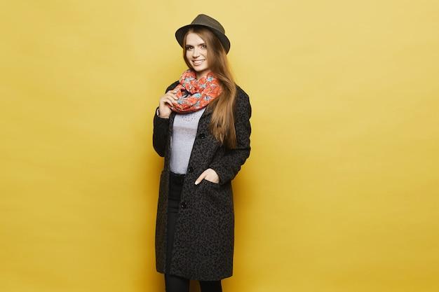 Ragazza bionda alla moda e bella in elegante cappotto con stampa leopardata, cappello alla moda e in posa sciarpa colorata