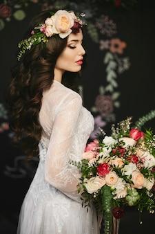 Ragazza alla moda e bellissima modella bruna con trucco luminoso e con una ghirlanda floreale in testa in un elegante abito di pizzo e con un grande mazzo di fiori di lusso in mano in posa all'interno
