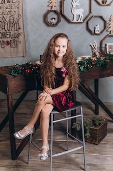 Bella ragazza alla moda in abito a casa vicino a capodanno e decorazioni natalizie e luci colorate