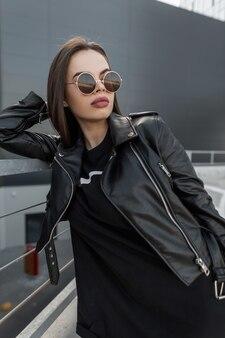 Donna bellissima modella alla moda con un bel viso naturale con occhiali vintage in giacca di pelle nera alla moda e felpa in tessuto in città