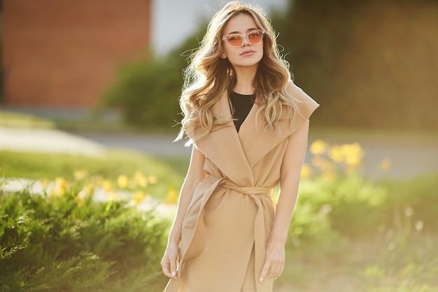 Alla moda bella e sensuale ragazza modella bionda in cappotto senza maniche e occhiali da sole alla moda gode del sole