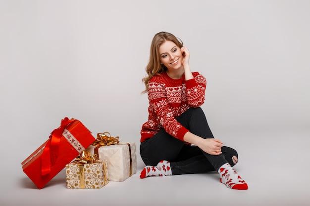 Bella donna alla moda con un sorriso in un maglione rosso vintage con calzini che si siede vicino a regali in studio