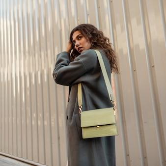 Bella giovane donna riccia alla moda in un elegante cappotto vintage con una borsa vicino a una parete di metallo. la bellezza e la moda delle donne