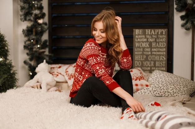 Bella ragazza alla moda in un maglione rosso alla moda si siede sul letto