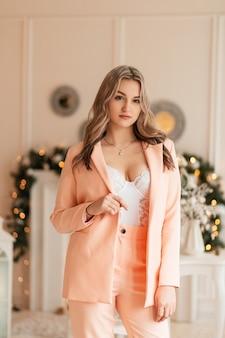 Bella ragazza alla moda in un abito elegante con un blazer e biancheria intima di pizzo bianco in una stanza su uno sfondo di decorazioni natalizie e luci