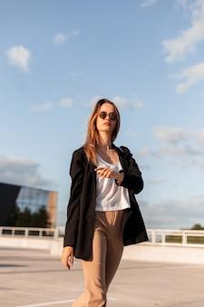 Bella giovane donna alla moda in giacca nera in pantaloni vintage in occhiali da sole alla moda in sexy top walksalks nel parcheggio della città in una giornata di sole estivo luminoso.