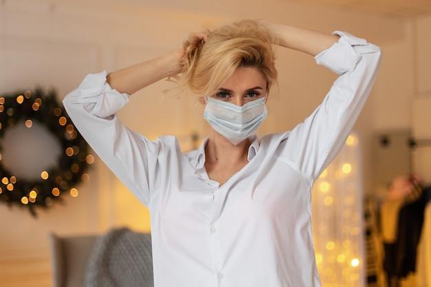Bella giovane donna alla moda con una maschera medica protettiva in una camicia casual bianca su uno sfondo di luci gialle e decorazioni natalizie a casa. vacanze e concetto di pandemia