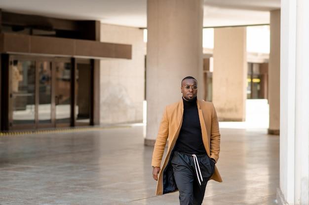 Uomo di colore alla moda che cammina in città