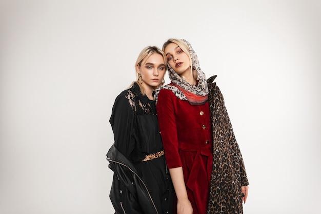 Donna bionda alla moda in elegante giacca nera giovanile oversize in guanti eleganti e modella ragazza con sciarpa sulla testa in lussuoso cappotto di leopardo posa al chiuso