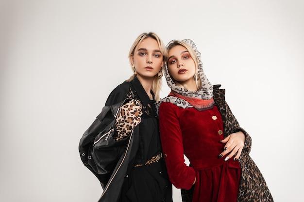 Donna bionda alla moda in elegante giacca nera giovanile oversize in guanti eleganti e modella ragazza con sciarpa sulla testa in lussuoso cappotto di leopardo in posa