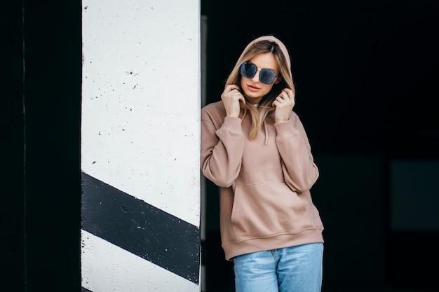 Donna bionda alla moda in felpa con cappuccio oversize marrone