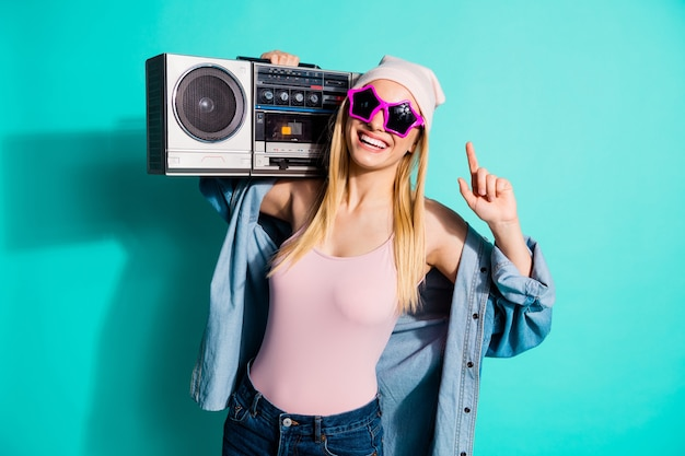 Donna bionda alla moda in posa contro il muro blu