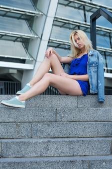 Donna bionda alla moda che indossa giacca di jeans seduta sulle scale della strada street