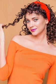 Ragazza bruna alla moda in un maglione arancione brillante e in bandana in posa sull'arancio
