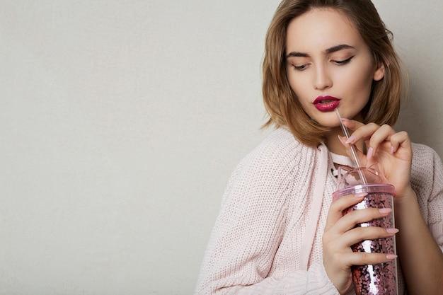 La modella bruna alla moda indossa un maglione rosa, bevendo cocktail in studio. spazio per il testo