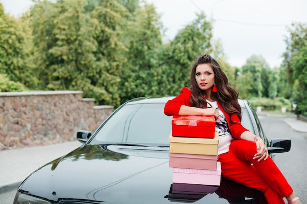 Castana alla moda in vestito rosso con l'acconciatura che posa sul paraurti dell'automobile con i contenitori di scarpe.