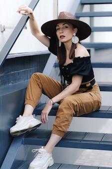 Donna castana alla moda con capelli lunghi, cappello di vimini grande alla moda che porta, che propone sulle scale.