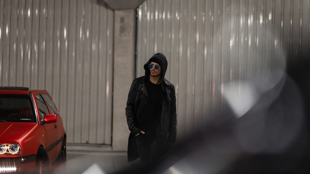 Modello alla moda uomo brutale con cappuccio con occhiali da sole in un'elegante giacca di pelle nera con una felpa con cappuccio cammina nel parcheggio di notte