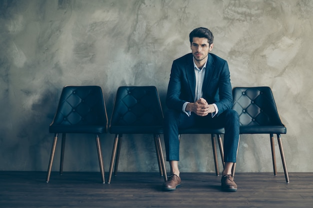 Uomo d'affari alla moda che propone contro il muro grigio