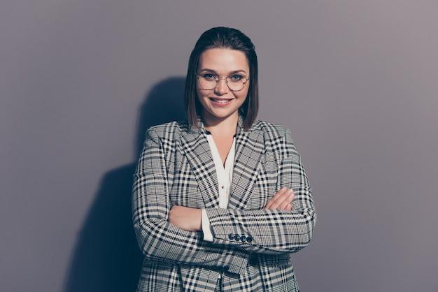 Donna di affari alla moda che indossa un blazer a scacchi in posa all'interno
