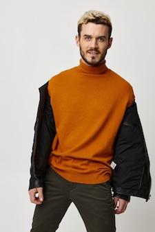 Un'auto alla moda con una giacca sbottonata e un maglione arancione ride su uno sfondo chiaro
