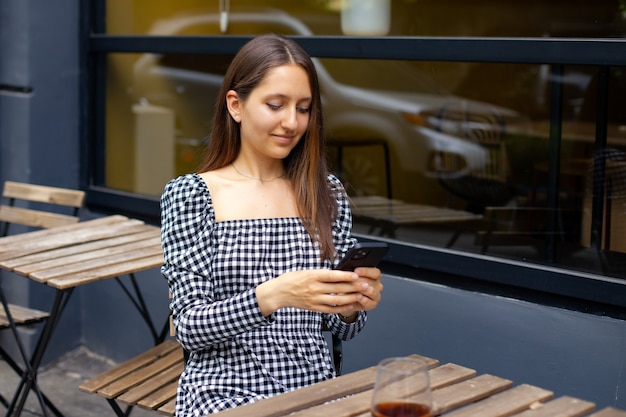Ragazza caucasica alla moda che usa il telefono mentre è seduta a un tavolo di legno vicino a un caffè sullo sfondo di una finestra