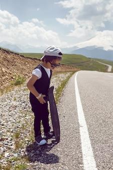 Ragazzo bambino alla moda in scarpe da ginnastica berretto bianco e gilet sta con un pattino sulla strada nelle montagne del monte everest in estate
