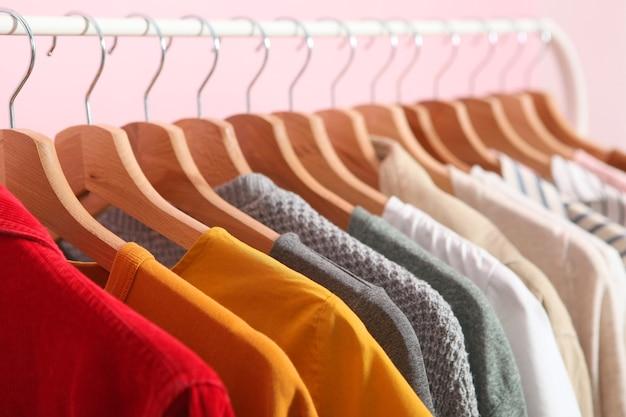 Vestiti alla moda appesi su un appendiabiti su uno sfondo colorato