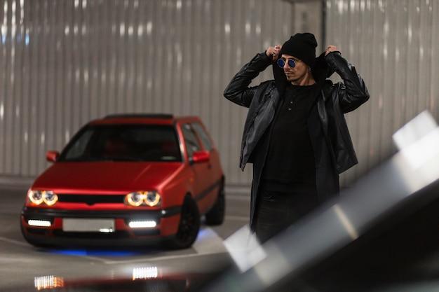 Giovane ragazzo alla moda con occhiali da sole alla moda in una giacca di pelle nera alla moda indossa un cappuccio vicino a un'auto rossa in un parcheggio di notte