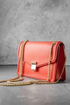 Borsa a tracolla alla moda rosso corallo su sfondo grigio cemento. borsa a tracolla realizzata in montone