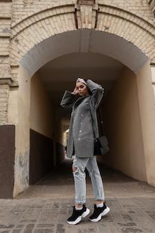 La giovane donna sveglia alla moda in bandana di bellezza di moda in cappotto alla moda grigio cammina vicino all'edificio d'epoca in città. bella ragazza in abiti alla moda cammina in città. look casual giovanile. nuova collezione primaverile.