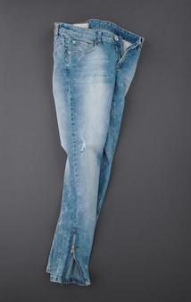 Pantaloni in denim alla moda su sfondo grigio, vista dall'alto