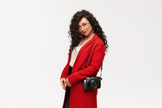 Donna elegante alla moda in cappotto rosso e occhiali da sole rotondi in posa da parte