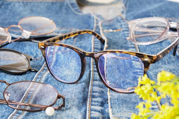 Occhiali alla moda su una giacca di jeans, una vecchia giacca fatta di blue jeans e occhiali multipli, montature per occhiali alla moda
