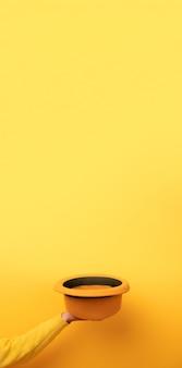 Cappello di feltro alla moda in mano su sfondo giallo