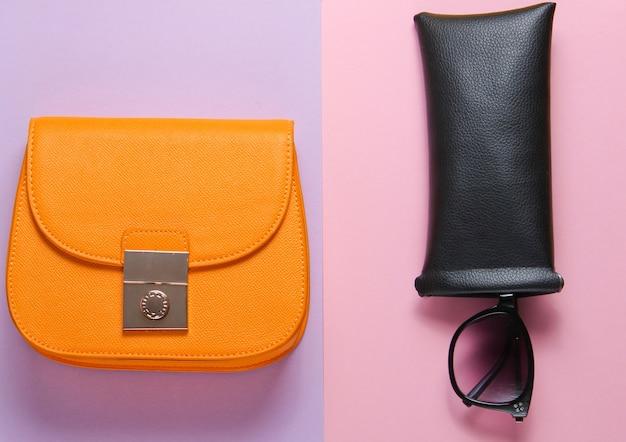 Accessori femminili alla moda su fondo di carta pastello. portafoglio in pelle alla moda, borsa, occhiali da sole in custodia protettiva. vista dall'alto