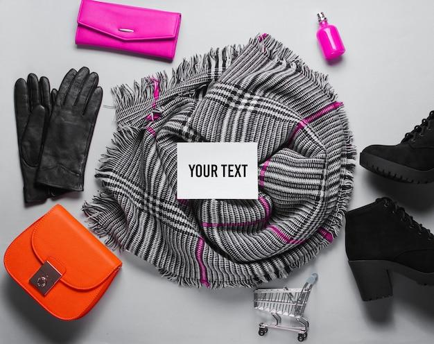 Accessori femminili alla moda shopaholic su sfondo grigio. mini carrello della spesa, borsa, stivali, bottiglia di profumo, portafoglio, guanti, sciarpa su sfondo grigio. copia spazio