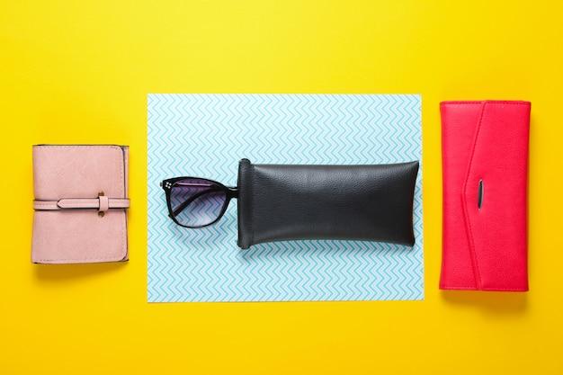Accessori femminili alla moda. portafogli in pelle alla moda, occhiali da sole in una custodia protettiva. vista dall'alto