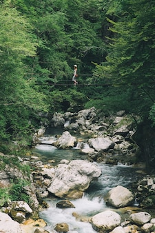 Ragazza alla moda rilassante stile di vita all'aperto con foresta e fiume di montagna sullo sfondo