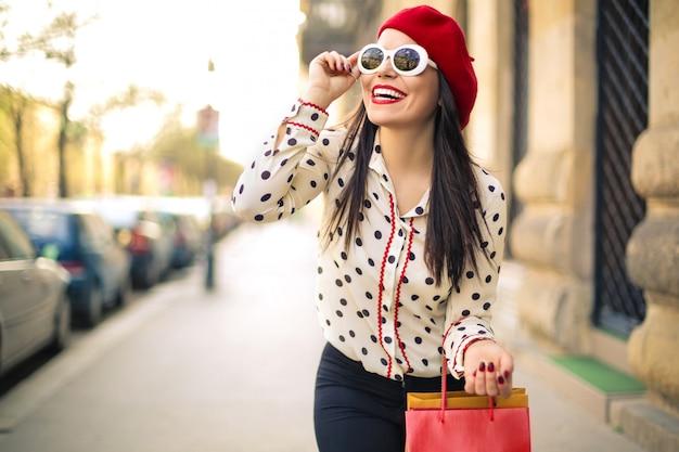Ragazza alla moda che cammina per la città con abiti fantastici