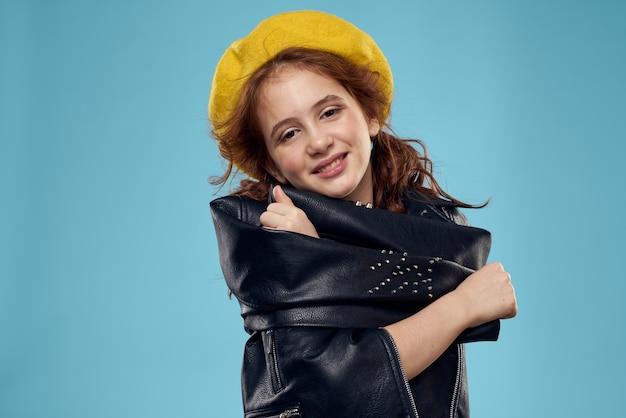 Ragazza alla moda in un berretto giallo e giacca di pelle a strisce sfondo blu della maglietta