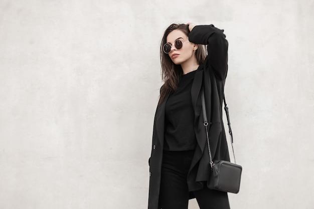 Splendida donna alla moda con occhiali da sole alla moda indossa abiti della nuova collezione primaverile alla moda per i giovani. modello di moda ragazza cool in abito nero casual vicino al muro bianco in città. stile di strada.