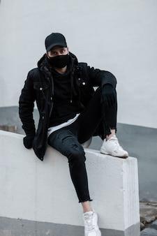 Ragazzo alla moda in abiti neri alla moda con berretto di design nero, giacca, felpa con cappuccio, jeans e scarpe da ginnastica bianche con una maschera protettiva seduta all'esterno