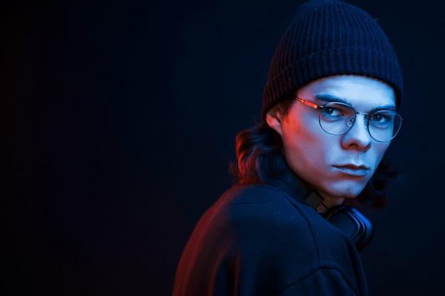 Ragazzo alla moda. studio girato in studio scuro con luce al neon. ritratto di uomo serio