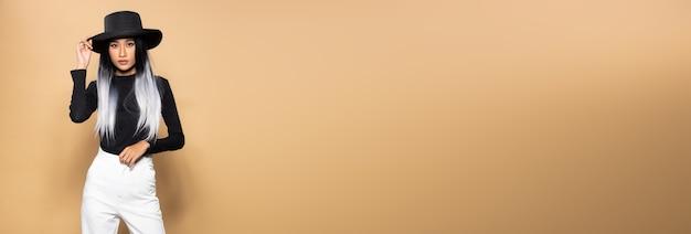 Stile di capelli alla moda ragazza asiatica con pantaloni bianchi cappello nero