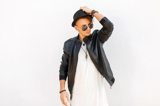 Alla moda bell'uomo in un elegante cappotto nero e cappello con occhiali da sole in posa vicino al muro di metallo bianco