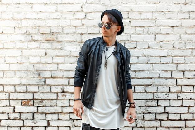 Uomo bello alla moda in vestiti alla moda che posano vicino a un vecchio muro di mattoni bianchi